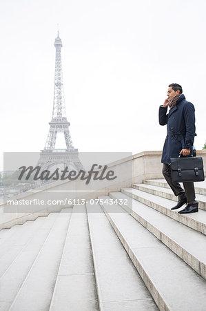 Businessman talking on cell phone on steps near Eiffel Tower, Paris, France