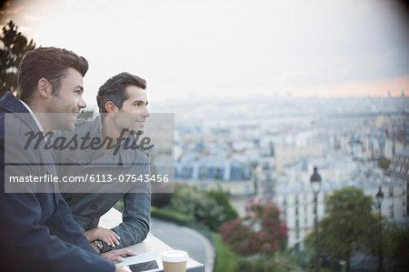 Businessmen overlooking cityscape, Paris, France