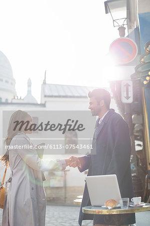 Business people shaking hands at sidewalk cafe, Paris, France
