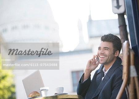 Businessman talking on cell phone at sidewalk cafe near Sacre Coeur Basilica, Paris, France