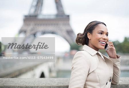 Businesswoman talking on cell phone near Eiffel Tower, Paris, France