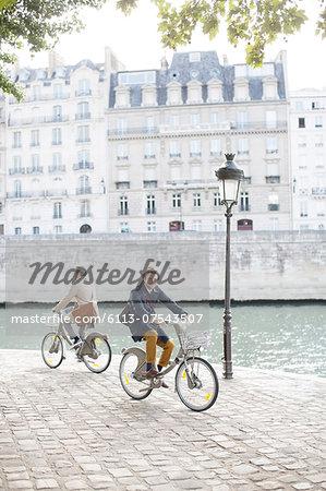 Men riding bicycles along Seine River, Paris, France
