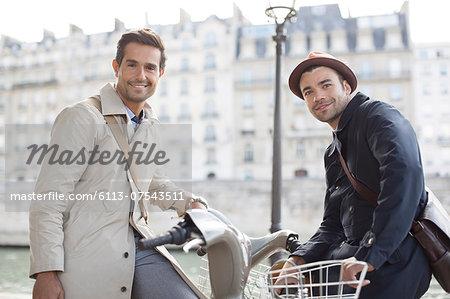 Businessmen on bicycles along Seine River, Paris, France