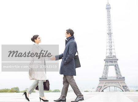 Business people shaking hands near Eiffel Tower, Paris, France