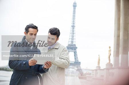 Businessmen using digital tablet near Eiffel Tower, Paris, France