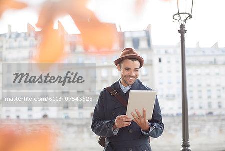 Businessmen using digital tablet along Seine River, Paris, France