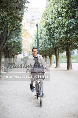Businessman riding bicycle in park, Paris, France
