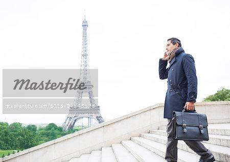 Businessmen on cell phone on steps near Eiffel Tower, Paris, France
