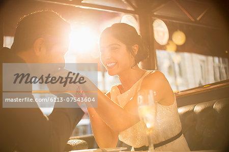 Man kissing girlfriend's hand in restaurant