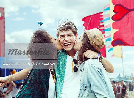 Women kissing man's cheek at music festival