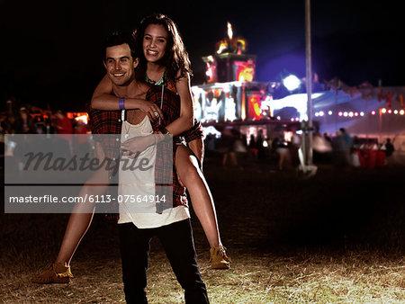 Portrait of man piggybacking woman at music festival