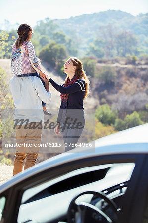 Happy family at roadside outside car