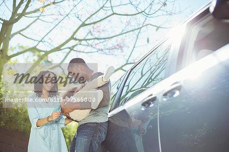 Happy family outside car