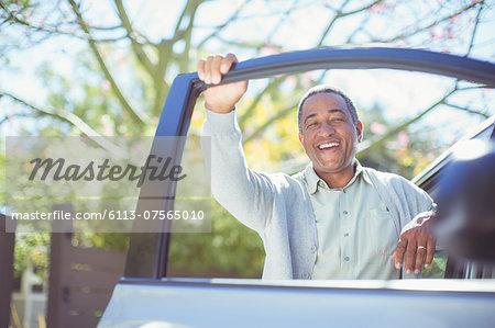 Portrait of happy senior man leaning on car door