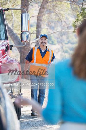 Roadside mechanic arriving to help woman