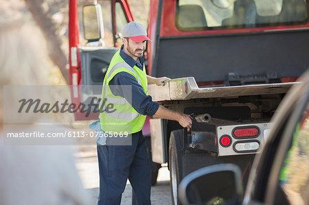 Roadside mechanic preparing to tow car