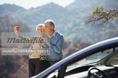 Senior couple taking self-portrait at roadside outside car
