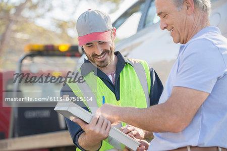 Man signing paperwork for roadside mechanic