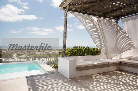 Curtains blowing in wind on luxury poolside patio overlooking ocean
