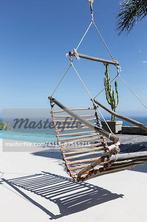 Hanging wooden chair on luxury patio overlooking ocean
