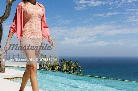 Woman walking along swimming pool overlooking ocean