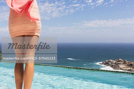 Woman in dress at poolside overlooking ocean