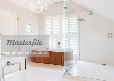 Chandelier over soaking tub in modern bathroom