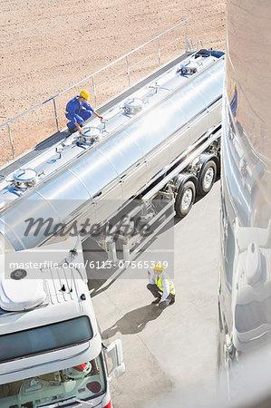 Workers around stainless steel milk tanker