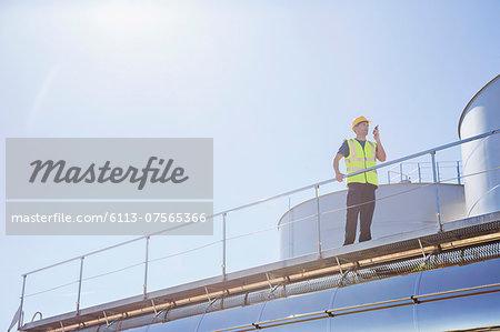 Worker using walkie-talkie on platform next to silage storage towers
