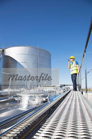 Worker using walkie-talkie on platform above stainless still milk tanker