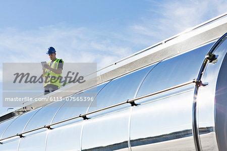 Worker using digital tablet on platform above stainless steel milk tanker