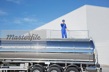 Worker talking on cell phone on platform above stainless steel milk tanker