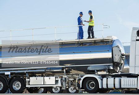 Workers on platform above stainless steel milk tanker