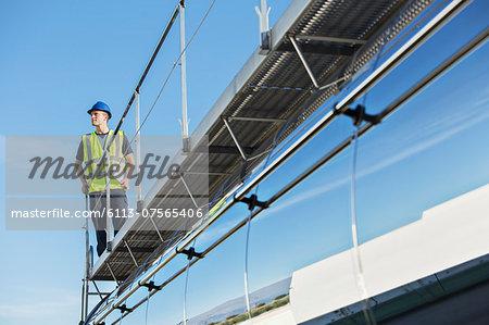 Worker on platform above stainless steel milk tanker