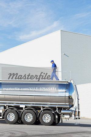Worker walking on platform above stainless steel milk tanker