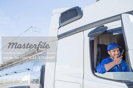 Driver using walkie-talkie in stainless steel milk tanker