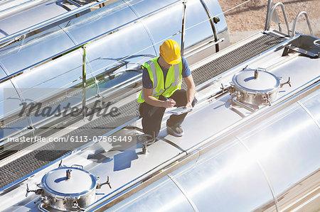 Worker using digital tablet on top of stainless steel milk tanker