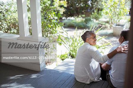 Senior couple hugging on porch