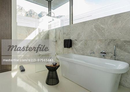 Soaking tub in sunny modern bathroom