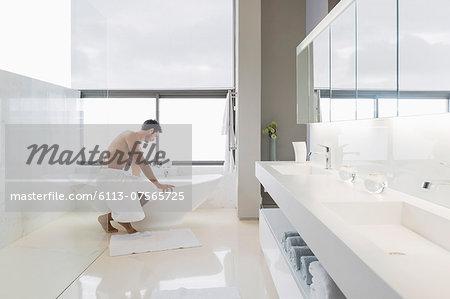Man in towel preparing bath