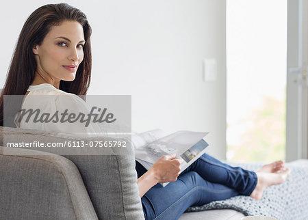 Portrait of confident woman reading magazine on chaise lounge