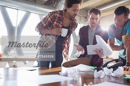 Creative businessmen reviewing paperwork in meeting