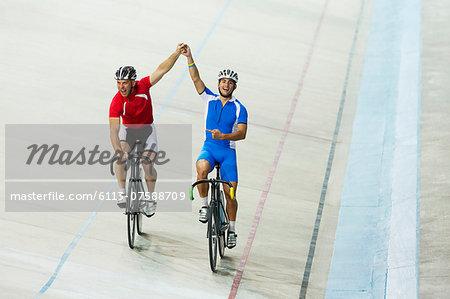 Track cyclists celebrating in velodrome