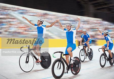 Track cycling team celebrating in velodrome