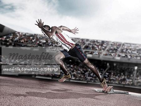 Runner taking off from starting block on track