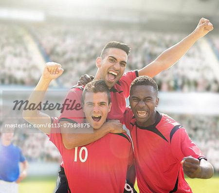 Soccer players celebrating on field