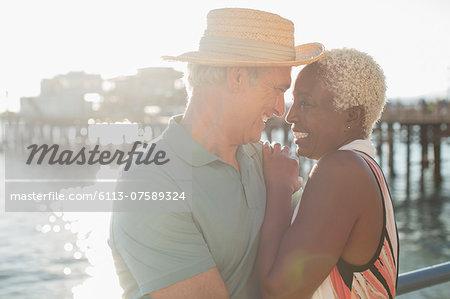 Senior couple hugging on pier