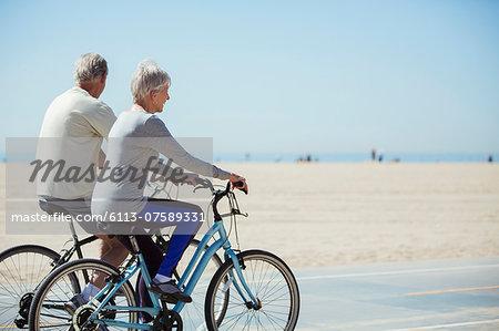 Senior couple riding bicycles on beach