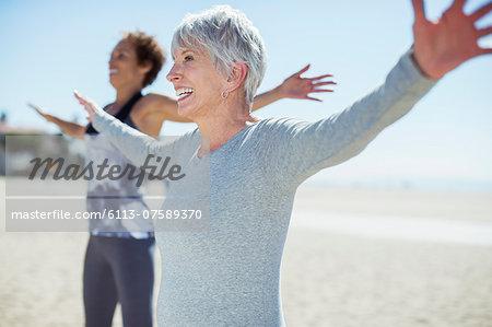 Senior women stretching arms on beach