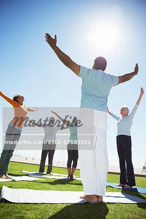 Seniors practicing yoga in sunny park